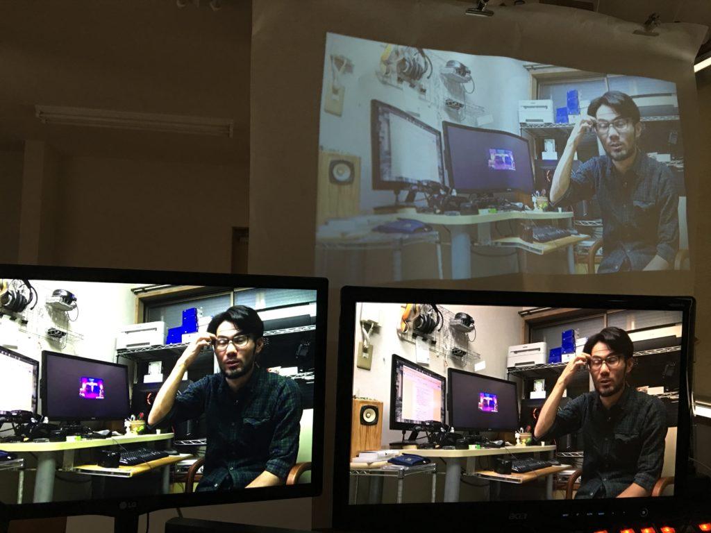 PCモニタ2台の奥に小型プロジェクタ用のスクリーンを設置して3画面にしている様子